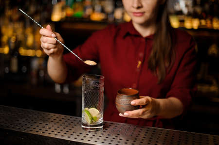 Female bartender putting a cane sugar into a glass with spoon at the steel bar counter Stock Photo