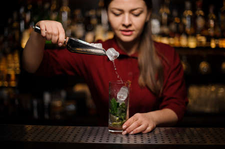 Female bartender adding an ice to the cocktail of lime, mint leaves and cane sugar Stock Photo