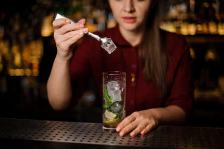 Female bartender adding an ice with tongs to the cocktail of lime, mint leaves and cane sugar