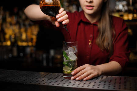 Female bartender adding a liquor to the cocktail of lime, ice, mint leaves and cane sugar Stock Photo