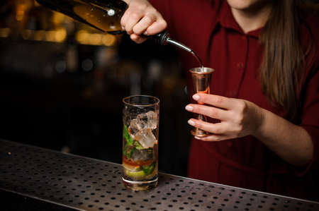 Female bartender filling a liqour to the measuring pile for preparing a delicious fresh cocktail Stock Photo