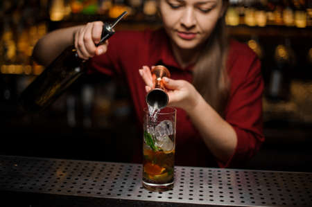 Female bartender filling a liqour from the measuring pile for preparing a delicious fresh cocktail