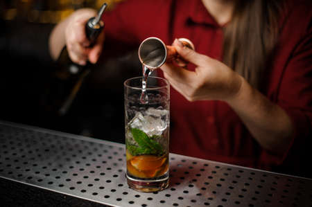 Female bartender pouring out an alcoholic drink from the measuring pile for preparing a delicious fresh cocktail