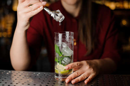 Female bartender adding an ice cube with tongs to the cocktail of lime, mint leaves and cane sugar