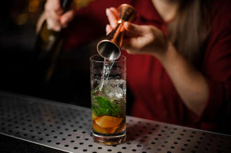 Female bartender pouring out a transparent alcoholic drink from the measuring pile for preparing a delicious fresh cocktail Stock Photo