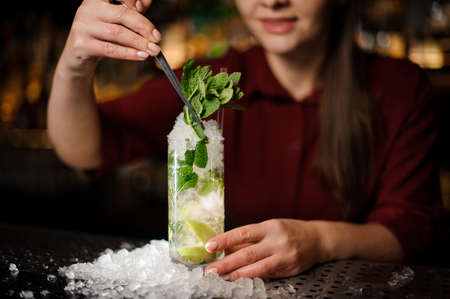 Female bartender adding more mint to a fresh delicious cocktail Caipirinha, which standing on the steel bar counter