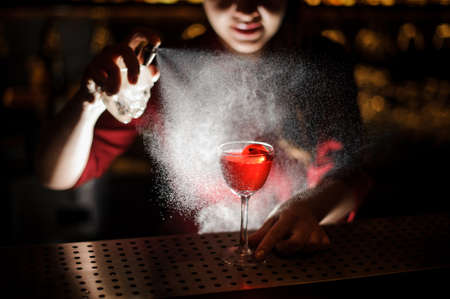 Female bartender spraying on a fresh delicious cocktail for serving it on the steel bar counter