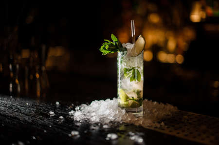 Fresh delicious cocktail Caipirinha with lime, mint and ice standing on the steel bar stand under the spotlight