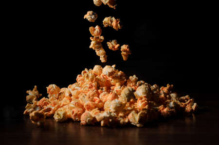 airy grains of yellow delicious roasted popcorn fall down on a black background on a wooden surface