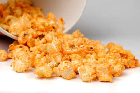 yellow delicious roasted fragrant spicy popcorn scattered from a bucket on a white background close up
