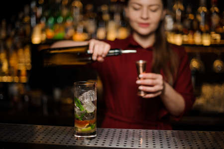 barmaid prepares a mojito in a crystal glass, adding dark rum and using bar equipment Stock Photo