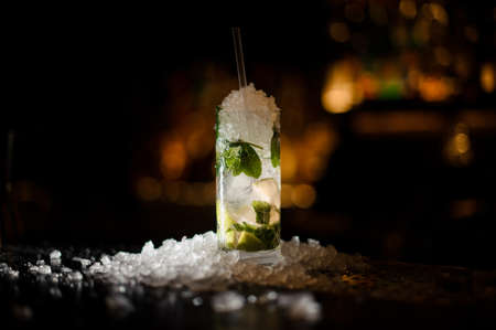 alcoholic cocktail mojito in a crystal glass, strewn with chipped ice, stands on a bar counter on a dark background