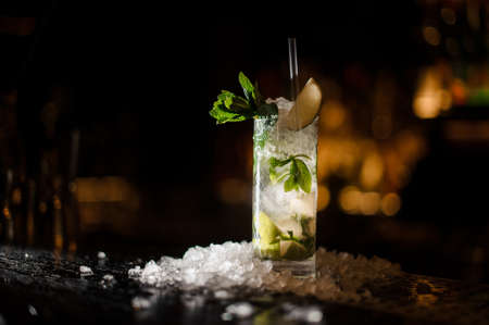 alcoholic cocktail mojito, strewn with chipped ice, stands on a bar counter on a dark wooden background Stock Photo