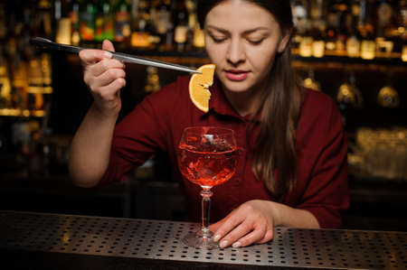 barmaid in a red dress finishes the preparation of an alcohol cocktail Spritz Veneziano, adding a slice of orange