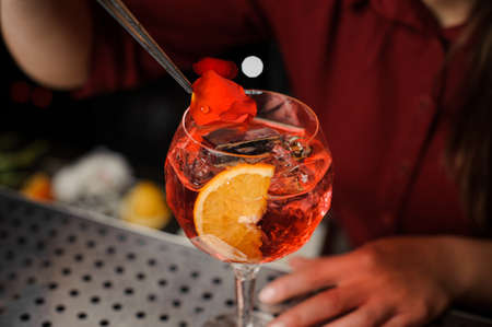 barmaid in a red dress finishes the preparation of an alcohol cocktail Spritz Veneziano, adding a rose petal Stock Photo