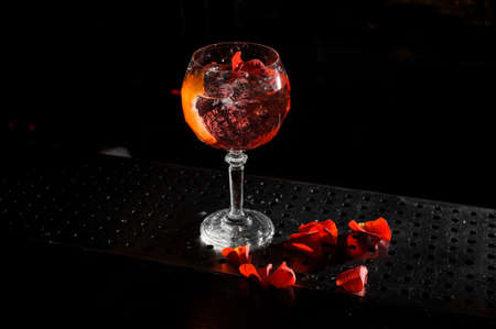 alcoholic cocktail Spritz Veneziano in a crystal glass stands on the bar, and next to it lie the petals of a red rose
