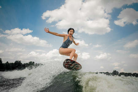 Screaming young woman jumping on the board wakesurfing on the river against the cloudy sky