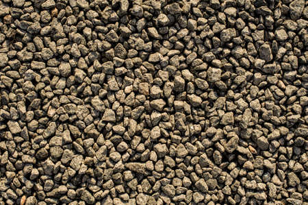 Texture background wallpaper of large amount of grey pebbles stone arranged under the sun light