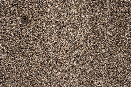 Texture background wallpaper of a large amount of grey pebbles stone arranged under the sun light