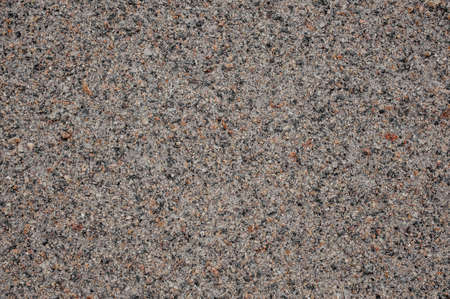 Close up texture of background wallpaper top view of grey grain asphalt with pieces of tiny stones in it
