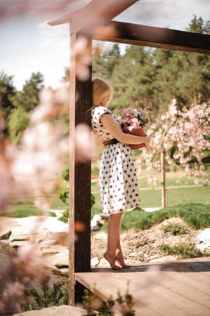 Beautiful blonde girl, dressed in a white black dotted dress, standing in the arbour with a pink box of beautiful flowers Stock Photo