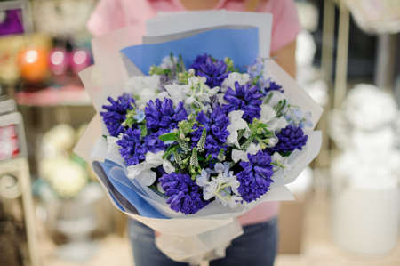 Girl in a pink shirt holding in her hands a beautiful big bouquet of blue and white tender flowers