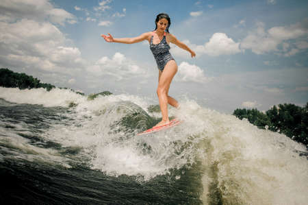 Young beautiful woman riding on the pink wakeboard on the lake on the background of beautiful sky Stock Photo