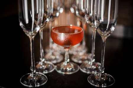 Elegant cocktail glass filled with tasty and sweet red alcoholic cocktail among empty champagne glasses on the table Stock Photo