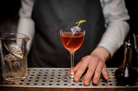 Bartender with a cocktail glass filled with summer drink decorated with a little rose bud Stock Photo