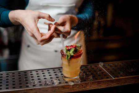 Girl splashing with sequins on the orange cocktail decorated with red flower with green leaves, lime and burning rafinated sugar Banque d'images