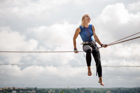Young smiling blondie woman sitting on the slackline rope on the background of clear sky Фото со стока