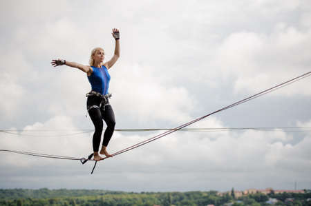 Young blondie woman balancing on the slackline rope on the background of clear blue sky