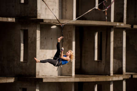 Young female equilibrist hanging on the slackline upside down on the background of unfinished building