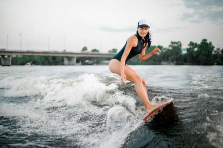 Young smiling active brunette girl riding on the wakesurf on high wave of motorboat on the river Zdjęcie Seryjne