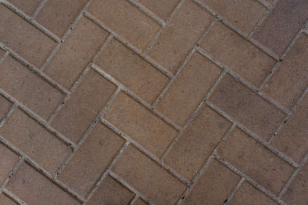 Top background macro photography of brown paving brick rectangular shaped pavement slab with gaps of concrete