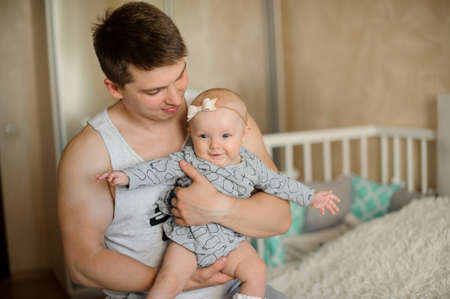 Happy smiling father holding a cute newborn baby girl in his arms in the bedroom Фото со стока - 106589877
