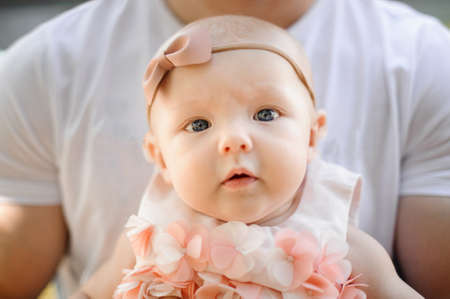 Portrait of little cute baby girl dressed in pink dress and bow in father hands