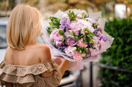 Rear view blonde woman in beige dress holding in her hands a bouquet of tender pink and violet flowers decorated with green leaves