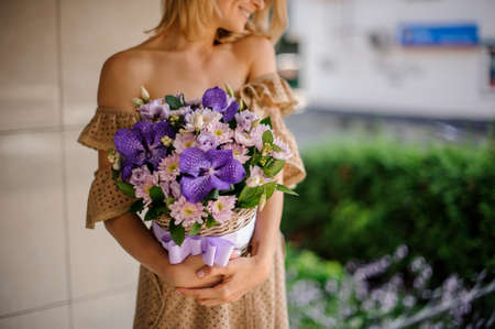 Young smiling girl in beige dress holding in her hands a basket of pink chrisantemum and violet orchids decorated with green leaves