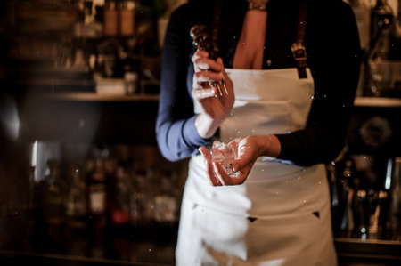 Female barman crushing a piece of ice for making a fresh summer cocktail on bar counter Stock Photo