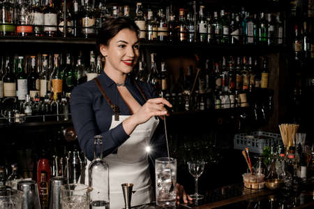 Beautiful smiling barman woman stirring fresh summer drink in a cocktail glass on the bar counter Stock Photo