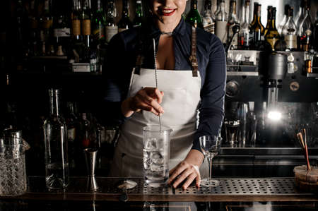 Smiling barman woman with deep neckline stirring cocktail with ice in a glass on the bar counter