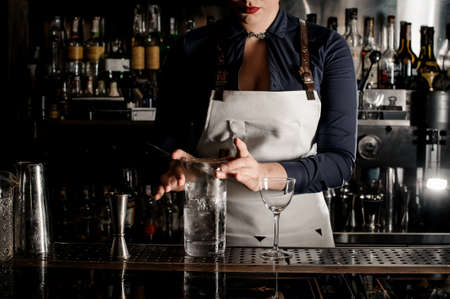 Barman woman with deep neckline stirring cocktail with ice in a glass on the bar counter