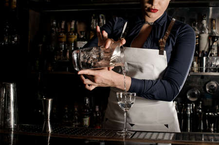 Beautiful barman woman pouring fresh summer drink into an elegant cocktail glass on the counter Stock Photo