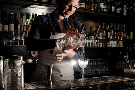 Beautiful smiling barman woman pouring fresh summer drink into an elegant cocktail glass on the counter