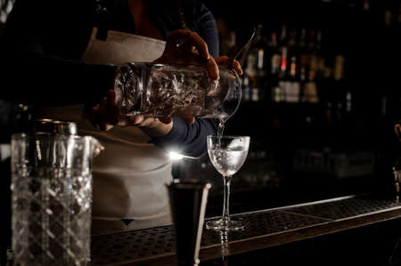 Barmaid hand pouring fresh summer drink into an elegant cocktail glass on the dark bar counter
