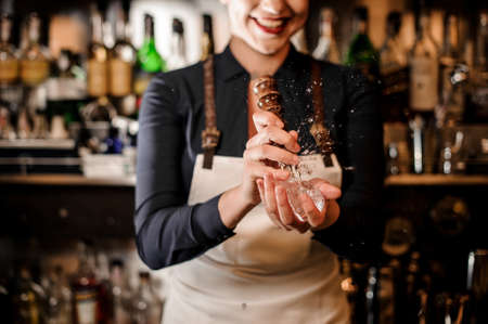 Smiling barman girl crushing a piece of ice for making a fresh summer cocktail on bar counter