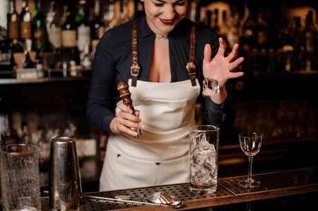 Sexy barman girl putting a piece of ice into a cocktail glass for making fresh summer drink Stock Photo