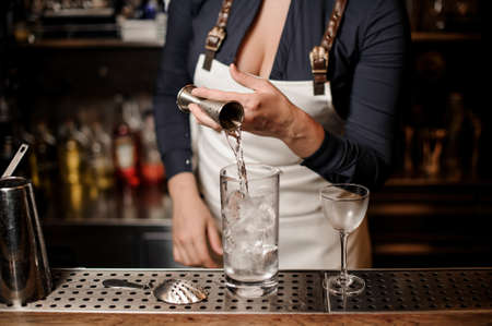 Sexy female barman pouring vodka into a cocktail glass with ice for making summer drink