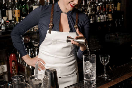 Sexy smiling female barman pouring vodka into a cocktail glass with ice for making summer drink Stock Photo